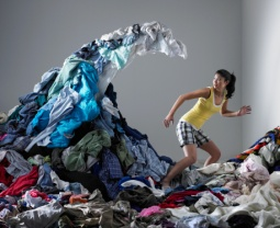 Woman underneath wave of laundry